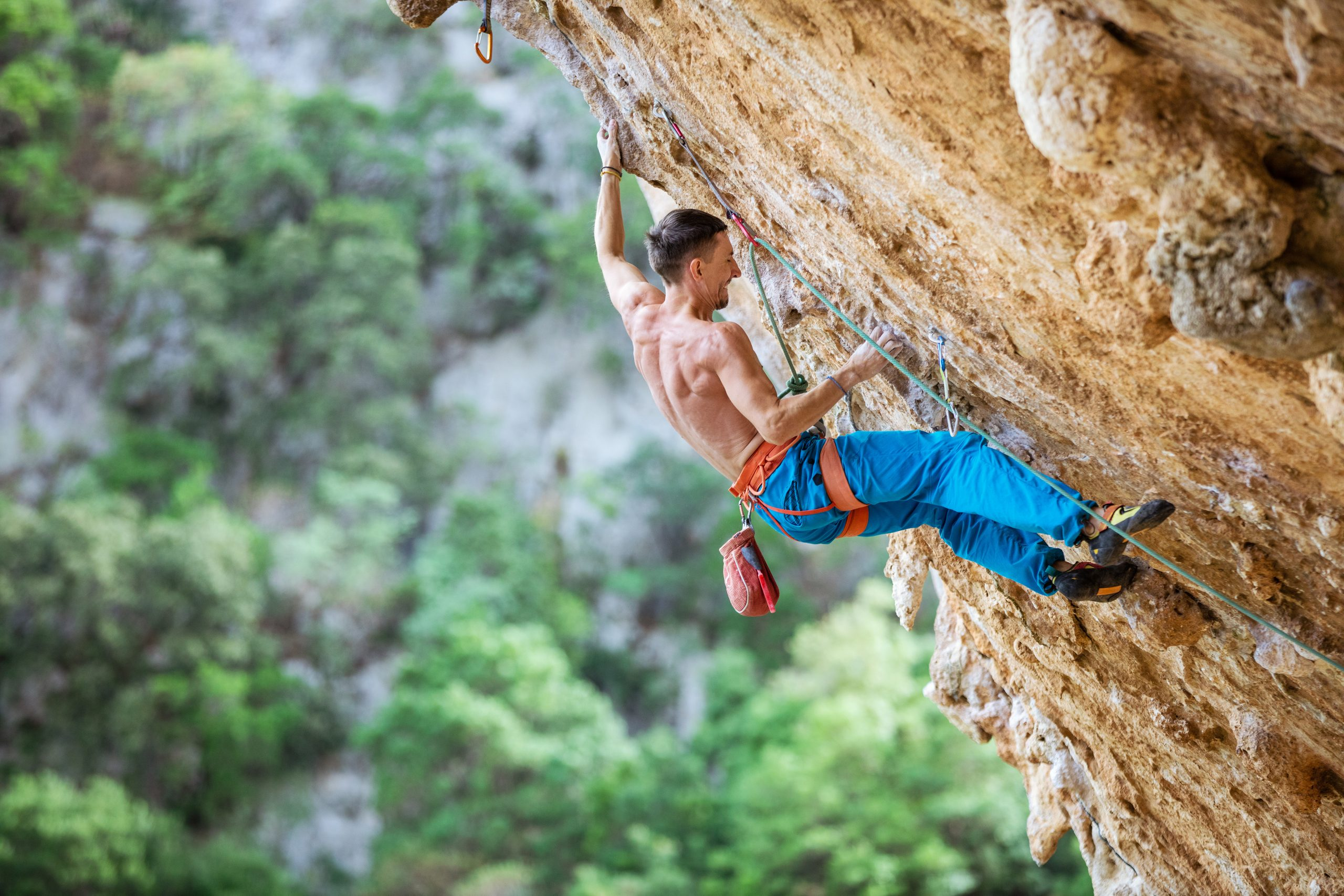 Male climber trying hard to grip small handholds on challenging